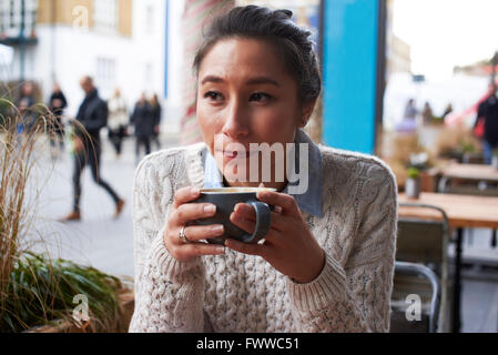 Young Woman Relaxing in Coffee Shop Banque D'Images