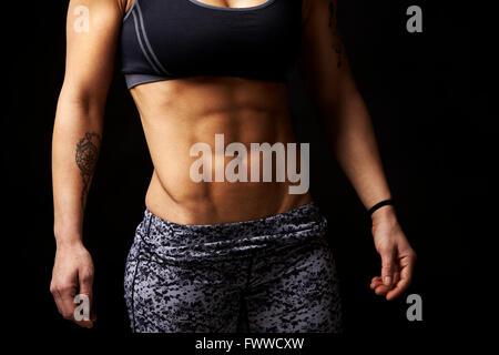 La mi-section de récolte de jeune femme musculaire des bras et abs Banque D'Images