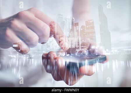Les mains de l'homme touchant, smartphone, double exposition avec gros plan sur la ville moderne