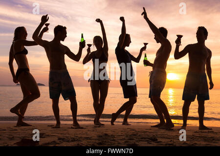 Beach Party, groupe de jeunes amis de la danse, boire de la bière et des cocktails au coucher du soleil Banque D'Images