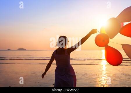 Concept de bonheur, heureuse fille aux ballons multicolores, de la joie et des émotions positives Banque D'Images