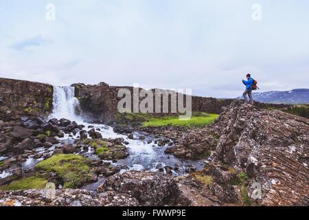 Voyageur backpacker taking photo de cascade avec un téléphone mobile Banque D'Images