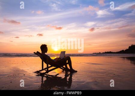 Silhouette d'happy business man with laptop travaillant sur la plage