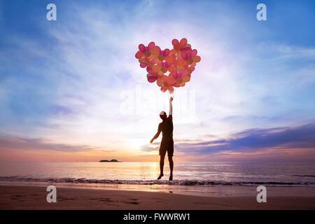 Concept L'amour, l'homme avec l'aide de ballons coeur battant, tomber en amour Banque D'Images