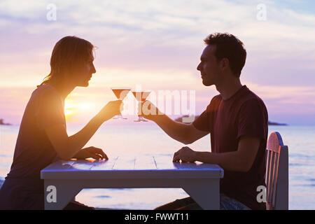 Couple in restaurant, boire des cocktails sur la plage au coucher du soleil Banque D'Images