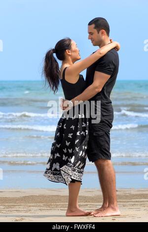 Romantic couple on beach.Young happy couple interracial à la recherche d'un l'autre et souriant sur la plage. Femme Asiatique,man
