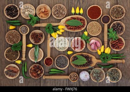 D'épices et d'herbes Chili ingrédients dans des bols en bois, cuillères et lâche sur un chêne de l'arrière-plan. Banque D'Images