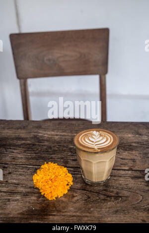 Cafe latte en verre avec latte art et orange fleur sur table en bois et une chaise en arrière-plan Banque D'Images