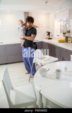 En Suède, le père tenant son (12-17 mois) dans la cuisine Banque D'Images