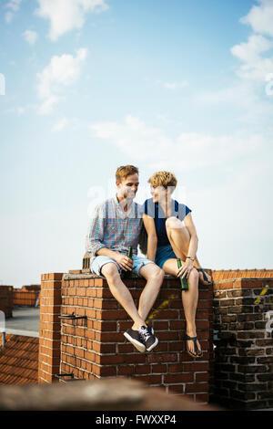 Allemagne, Berlin, Young couple holding beer sur le toit Banque D'Images