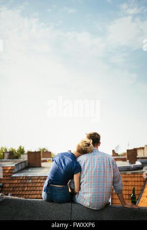 Allemagne, Berlin, jeune couple assis sur le toit avec de la bière Banque D'Images