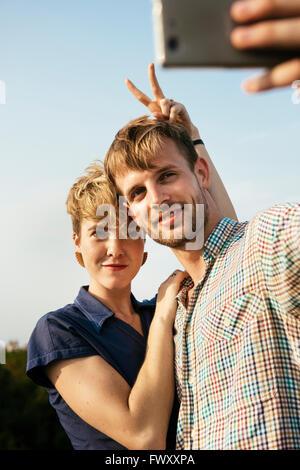 Allemagne, Berlin, Young couple hugging et en tenant avec selfies smart phone Banque D'Images