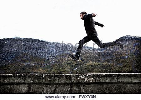 La Norvège, Odda, Man jumping over mur de pierre Banque D'Images