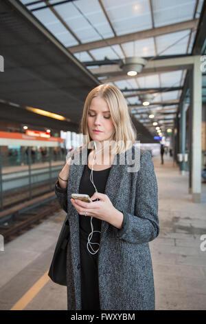 La Finlande, Helsinki, Uusimaa, jeune femme à l'aide du smartphone sur le Métro d'Helsinki Banque D'Images