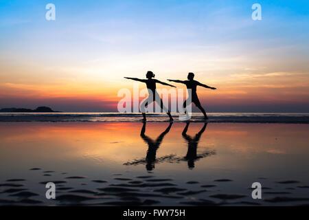 Groupe de personnes pratiquant le yoga, couple d'étirements sur la plage au coucher du soleil Banque D'Images