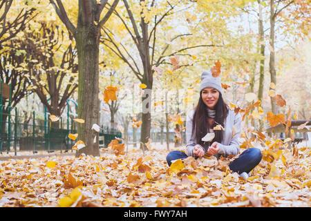 Autumn park, belle femme souriante et la chute des feuilles jaunes Banque D'Images