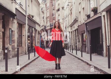 Belle femme, portrait de fille avec parapluie rouge debout sur la rue de Paris Banque D'Images
