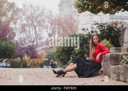 Belle femme en rouge, portrait of caucasian fashion jeune modèle aux cheveux longs assis tout seul, la psychologie Banque D'Images