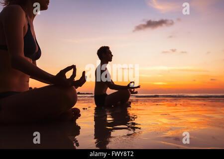 Groupe de personnes méditant sur la plage, le yoga et la santé Contexte Banque D'Images