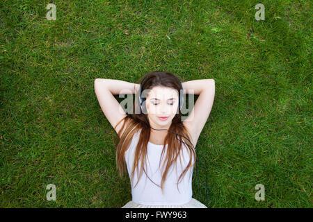 Profitez de la musique, vue de dessus de jeune femme dans les écouteurs, l'arrière-plan Banque D'Images