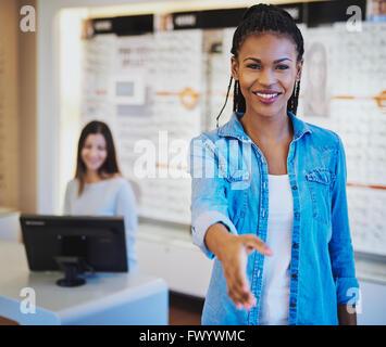 Pretty young African American optométriste saluant un client à la porte avec un sourire rayonnant et main tendue Banque D'Images