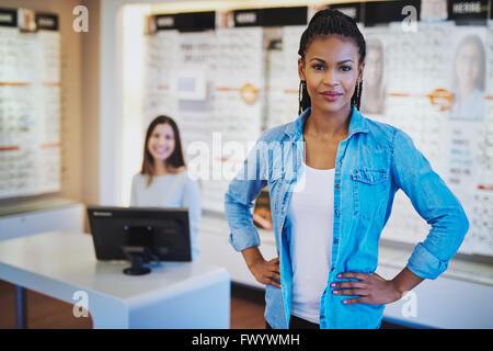 Jeune femme noire smiling standing dans son magasin avec un collègue en backgorund Banque D'Images