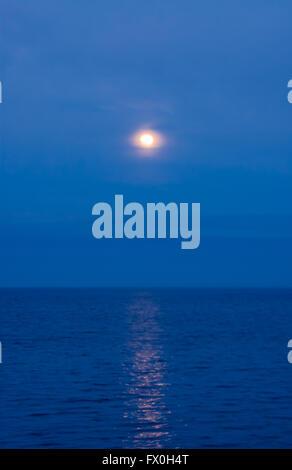 Soft moon dans les nuages et la brume reflétée dans l'eau sur bleu ciel du soir. Banque D'Images