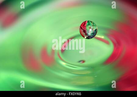 L'eau qui tombe goutte et de belles vagues sur fond coloré. Banque D'Images