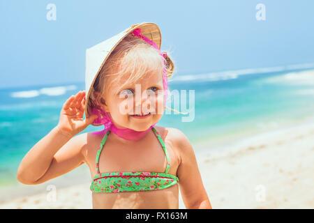 Portrait de la belle petite traveler par beau plage de sable blanc - happy smiling baby girl en chapeau de paille Banque D'Images