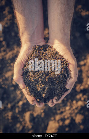 Farmer holding pile de terres arables et l'examen de sa qualité sur des terres agricoles fertiles, homme d'agronome Banque D'Images