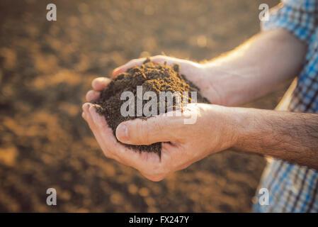 Farmer holding pile de sols arables en mains, responsable et durable de la production agricole, Close up avec selective Banque D'Images