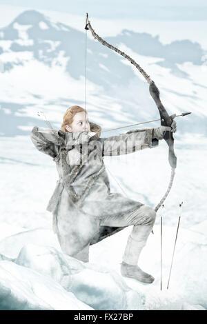 Fille sauvage archer dans la neige avec bow Banque D'Images