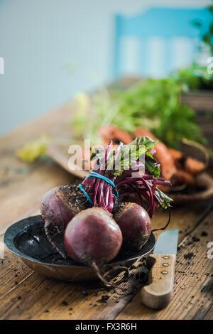 Betterave frais entier de sol de jardin, table de ferme en bois dans la cuisine Banque D'Images