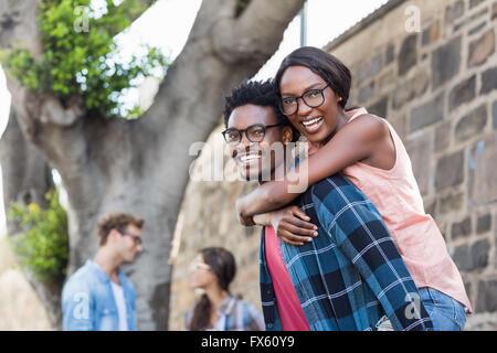 Young man giving piggyback pour femme Banque D'Images