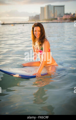 Mixed Race amputee assis sur une planche de surf dans la région de ocean