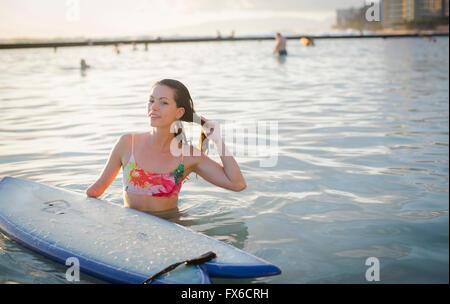 Mixed Race amputée avec surfboard in ocean