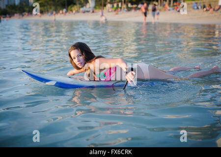 Mixed Race amputee natation with surfboard