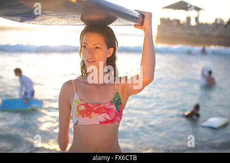 Mixed Race amputee transportant surfboard on beach