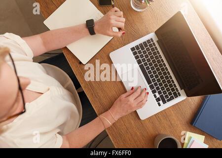 Vue de dessus d'une femme assise à son bureau et travaille sur ordinateur portable. Businesswoman working from home.