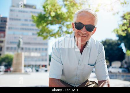 Portrait of happy senior man sitting en dehors de la ville. Homme mature avec des lunettes à l'extérieur sur une Banque D'Images