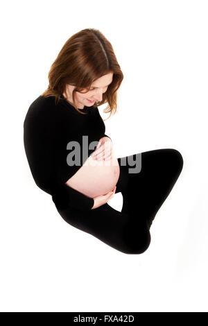Une mère assise en noir top et leggings regarde ses mains reposant sur son ventre enceinte on a white background Banque D'Images