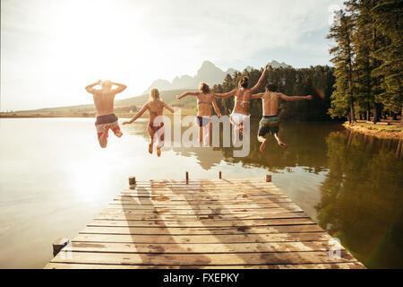 Portrait of young people jumping de la jetée dans le lac d'ensemble. Les amis de sauter la jetée sur le lac sur Banque D'Images