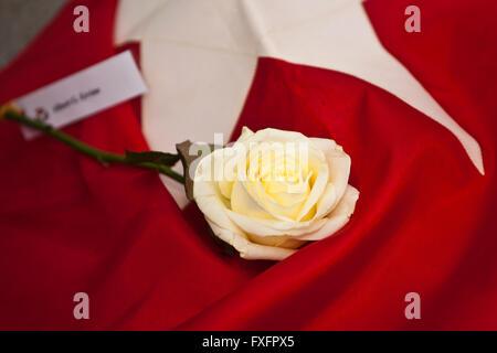 Belfast, Royaume-Uni. 15 avr, 2016.Une rose jaune sur un drapeau à la White Star Line Le Titanic Memorial à Belfast Banque D'Images