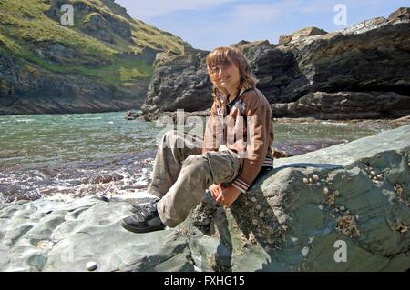 Jeune garçon est assis sur un rocher au bord de la mer à tintagel, Cornwall Banque D'Images