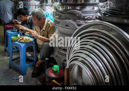 Les habitants de manger le déjeuner à l'intérieur du marché Binh Tay, Ho Chi Minh City, Vietnam Banque D'Images