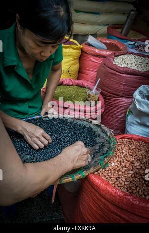 L'échantillonnage de personnes dans les haricots, le marché Binh Tay Ho Chi Minh City, Vietnam Banque D'Images