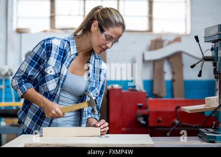 Femme tenant un marteau de charpentier à conduire des clous dans une planche en bois Banque D'Images