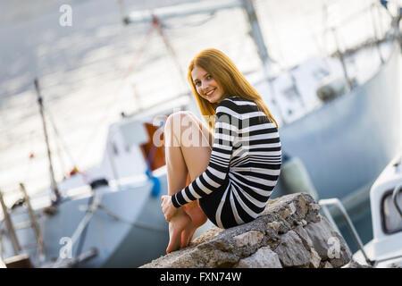 Adorable teengirl jeune fille posant avant le yacht dans la marina cachée jambes pieds nus-pieds souriants angle Banque D'Images