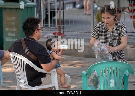 Young Asian family avec père biberon son bébé. S. E. Asie Thaïlande Banque D'Images