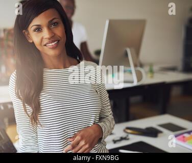 Superbe femme propriétaire d'entreprise unique en noir et blanc Chemisier rayé avec partenaire sur ordinateur en Banque D'Images